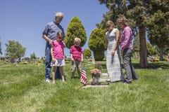 一起追悼在一个坟墓的家庭在公墓 免版税库存照片