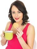 Νέα γυναίκα με μια κούπα του τσαγιού και του μπισκότου Στοκ εικόνα με δικαίωμα ελεύθερης χρήσης