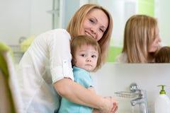 母亲在卫生间里教孩子洗涤的手 免版税库存图片