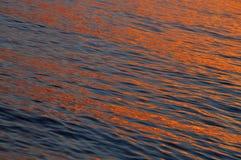 Θερμή να λάμψει χρώματος επιφάνεια νερού ηλιοβασιλέματος Στοκ Φωτογραφίες