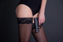 拿着在灰色的黑女用贴身内衣裤的美丽的性感的妇女枪 库存图片