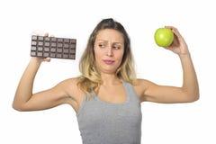 拿着苹果和巧克力块在健康果子的可爱的妇女对甜速食诱惑 免版税库存图片