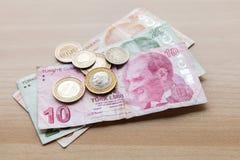 与阿塔图尔克画象的土耳其金钱在木桌上 库存照片
