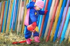 两岁女孩浇灌的土地在庭院里 免版税库存图片