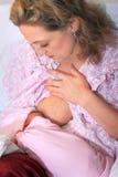 护理新出生的婴孩的新的妈妈 图库摄影