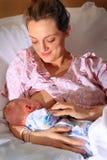 护理新出生的婴孩的愉快的妈妈 库存图片