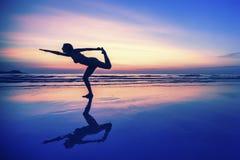 在日落期间,有反射的妇女,做在海滩行使 免版税库存照片