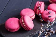 在黑背景的桃红色莓蛋白杏仁饼干 免版税图库摄影