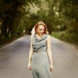 站立在路的年轻白肤金发的可爱的妇女 库存照片