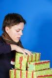 摆在与圣诞节礼物盒的十几岁的男孩 库存图片