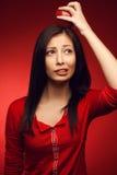 摆在红色背景的迷茫的学生女孩 免版税库存照片