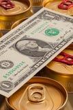 罐头啤酒和美元 库存照片