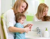 母亲在卫生间里教孩子洗涤的手 免版税库存照片