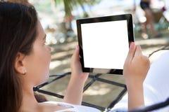 Γυναίκα που χρησιμοποιεί την ψηφιακή ταμπλέτα στην παραλία Στοκ Εικόνες