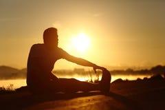舒展在日落的一个健身人的剪影 免版税库存照片