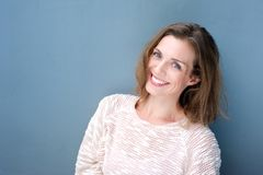 蓝色背景的可爱的微笑的中间妇女 免版税库存照片