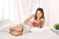 Сексуальная красивая женщина студента лежа на романе чтения кровати или изучая книга внутри ослабляют Стоковое Изображение