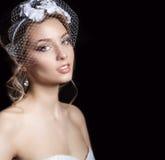 愉快的美丽的一套白色婚礼礼服的新娘妇女白肤金发的女孩,与头发和明亮的构成与面纱在她的眼睛和花 图库摄影