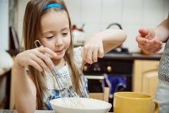 去小的女孩搅拌薄煎饼的面团 免版税库存照片