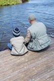 Рыбная ловля отца и сына на озере Стоковое фото RF