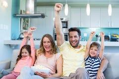 在长沙发的愉快的家庭看电视的 库存图片
