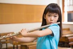 演奏长笛的逗人喜爱的学生在教室 免版税图库摄影
