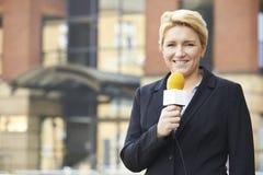 Θηλυκή ραδιοφωνική αναμετάδοση δημοσιογράφων έξω από το κτίριο γραφείων Στοκ φωτογραφία με δικαίωμα ελεύθερης χρήσης