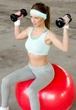 行使与哑铃和健身球的美丽的少妇 库存照片