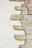 向灰泥墙壁扔石头 免版税库存照片
