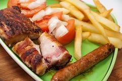 Μικτό ψημένο στη σχάρα κρέας που εξυπηρετείται με τη σαλάτα και τις τηγανιτές πατάτες ντοματών Στοκ εικόνες με δικαίωμα ελεύθερης χρήσης
