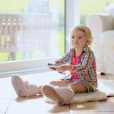 在家看电视的滑稽的小女孩 免版税库存图片