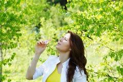 女孩打击泡影在春天 免版税图库摄影