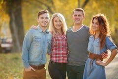Τέσσερις καλοί φίλοι χαλαρώνουν και έχουν τη διασκέδαση στο πάρκο φθινοπώρου Στοκ Φωτογραφία