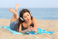 青少年的女孩听的音乐和唱歌在海滩 免版税库存图片