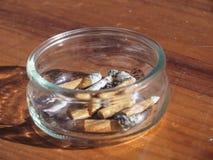 有香烟的圆的烟灰缸在一张木桌上 免版税库存照片