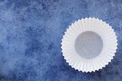 在蓝色背景的空的白色杯形蛋糕盒 库存照片
