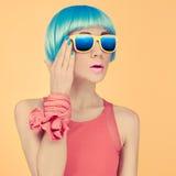 时尚在一顶蓝色假发和太阳镜的夫人惊奇 免版税库存照片