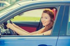 驾驶她新的蓝色汽车的愉快的美丽的少妇 免版税库存照片