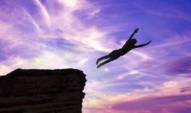 跳跃峭壁的一个人的剪影 免版税库存照片