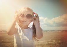假期有太阳镜的海滩女孩在温暖的太阳 库存照片