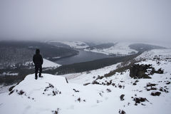 看往积雪的谷的山顶的人 免版税库存照片