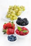 新鲜的庭院莓果和葡萄在一张白色木桌上 免版税库存照片