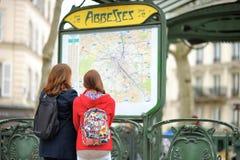 两看巴黎人地铁的地图游人 库存照片