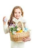 有篮子的微笑的小女孩有很多五颜六色的复活节彩蛋 免版税库存照片