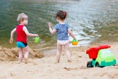 Λίγο παιχνίδι αγοριών και κοριτσιών μικρών παιδιών μαζί με τα παιχνίδια άμμου πλησίον Στοκ Εικόνες