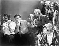 Человек говоря на телефоне и его друзьях смотря его и пробуя слушать (все показанные люди более длинные живущие и Стоковое Изображение