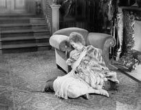 Молодая женщина сидя перед местом огня снованным в одеяле меха смотря унылый (все показанные люди более длинные живущие и Стоковые Фотографии RF