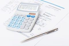 有银色笔的整洁的计算器和在它下的电费单 免版税库存图片