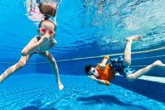 游泳的孩子在水面下 免版税库存照片