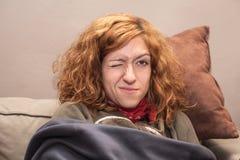 有一只眼睛的红头发人妇女结束了放松在沙发 免版税库存图片